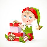 Cute little Santa`s elf sit and puts boxes with gifts Stock Photo
