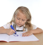 Cute little schoogirl happy on desk drawing on notepad with marker Stock Photos