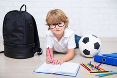 Cute little school boy in glasses doing homework Royalty Free Stock Photo