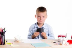 Cute little school boy with sad face sitting at his desk on whit stock image