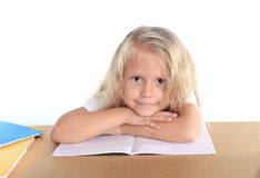 Cute little school girl happy on desk leaning in relax on book Royalty Free Stock Image
