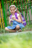 Cute little school-girl listening to music outside with white he. Young girl sitting next school fence and listening to music Stock Photos