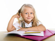 Cute  little school girl playing with her blonde hair sitting happy on desk Stock Photos