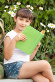 Cute Little School Girl Reading Book. Portrait of cute little school girl  sitting and reading book on background of summer green park Royalty Free Stock Images