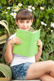 Cute Little School Girl Reading Book. Portrait of cute little school girl  sitting and reading book on background of summer green park Stock Photo