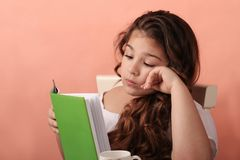 Cute little school girl reading book royalty free stock photos