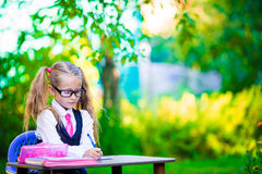 Cute little school girl writing at desk with Stock Images