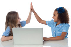 Cute little school girls with laptop. School girls giving high five with laptop Stock Images