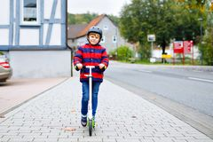 Cute little school kid boy with helmet riding on scooter in park nature. children activities outdoor in winter, spring. Or autumn. funny happy child in colorful stock image