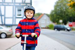 Cute little school kid boy with helmet riding on scooter in park nature. children activities outdoor in winter, spring. Or autumn. funny happy child in colorful royalty free stock images