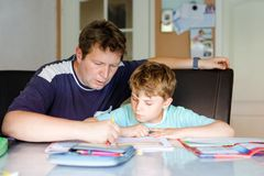 Cute little school kid boy at home making homework with dad. Little child writing with colorful pencils, father helping royalty free stock photography