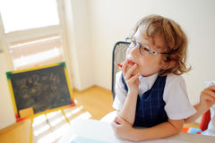 Cute little schoolboy in glasses has fallen into a reverie. The boy leaned his head on his hand and looking somewhere to the side. This elementary school Royalty Free Stock Photography