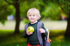 Cute little schoolboy with his backpack and apple. Back to school concept. Cute little schoolboy outdoors on sunny autumn day. Young student with his backpack Stock Image