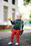 Cute little schoolboy with his backpack and apple. Back to school concept. Cute little schoolboy outdoors on sunny autumn day. Young student with his backpack Royalty Free Stock Image