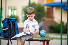Cute little schoolboy studying outdoors on sunny day. Young student doing his homework. Education for small kids. Back to school concept Stock Photo