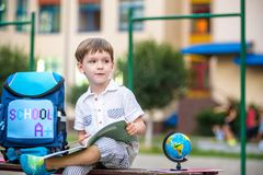 Cute little schoolboy studying outdoors on sunny day. Young student doing his homework. Education for small kids. Back to school concept Stock Images