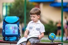 Cute little schoolboy studying outdoors on sunny day. Young student doing his homework. Education for small kids. Back to school concept Royalty Free Stock Photography