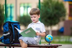 Cute little schoolboy studying outdoors on sunny day. Young student doing his homework. Education for small kids. Back to school concept Royalty Free Stock Photos