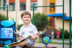 Cute little schoolboy studying outdoors on sunny day. Young student doing his homework. Education for small kids. Back to school concept Stock Photography