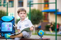 Cute little schoolboy studying outdoors on sunny day. Young student doing his homework. Education for small kids. Back to school concept Royalty Free Stock Images