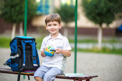 Cute little schoolboy studying outdoors on sunny day Royalty Free Stock Photos