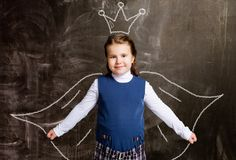 Schoolgirl against chalkboard, with drawn crown and cloak royalty free stock image