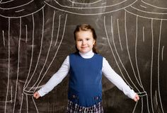 Schoolgirl against chalkboard, with drawn curtains royalty free stock photography