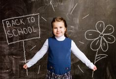 Schoolgirl against chalkboard, with drawn flower and plate royalty free stock photo