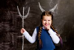 Schoolgirl against chalkboard, with horns of a devil and a tri stock image