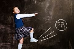 Schoolgirl against chalkboard, kicking a ball stock photo