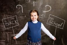 Cute little schoolgirl against chalkboard, with plate royalty free stock images