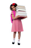 Cute little schoolgirl carrying stack of books Royalty Free Stock Images