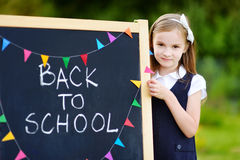 Cute little schoolgirl feeling excited about going back to school. Cute little schoolgirl feeling very excited about going back to school Stock Images