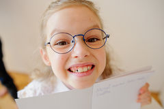 Cute little schoolgirl in glasses shows her copybook. Royalty Free Stock Photography
