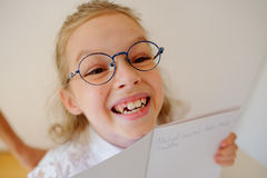 Cute little schoolgirl in glasses shows her copybook. Royalty Free Stock Image