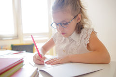 Cute little schoolgirl in glasses something diligently writes in a notebook. Royalty Free Stock Image