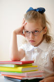 Cute little schoolgirl pondered. Stock Photo