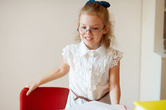 Cute little schoolgirl stands near desks. Royalty Free Stock Photos
