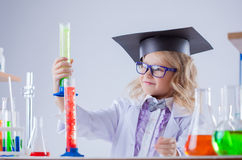 Cute little scientist interested looking at flasks Royalty Free Stock Photo