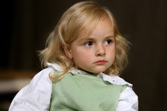 Cute little serious angel in green dress Stock Photo