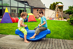 Cute little siblings swinging. On the home yard Stock Photos