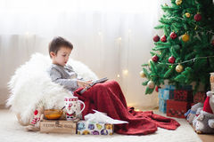 Cute little sick boy, sitting on bean bag, playing on tablet and Royalty Free Stock Photography