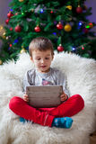 Cute little sick boy, sitting on bean bag, playing on tablet Royalty Free Stock Photography