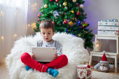 Cute little sick boy, sitting on bean bag, playing on tablet Stock Photos