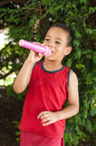 Cute little singer boy singing on the microphone in the city par. K surrounded by green vegetation royalty free stock images