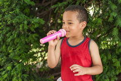 Cute little singer boy singing on the microphone in the city par Royalty Free Stock Photos