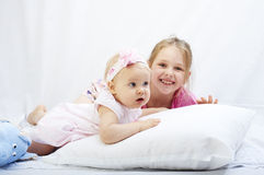 Cute little sister play with  newborn on a white background Stock Photos