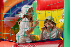 Cute little sisters in a jumping castle. Pretty young girls posing in a bouncing castle in a bright sunny day with beautiful smile Royalty Free Stock Photo