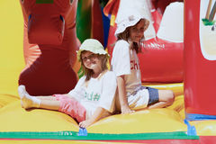 Cute little sisters in a jumping castle. Pretty young girls posing in a bouncing castle in a bright sunny day with beautiful smile Royalty Free Stock Photos
