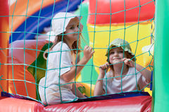 Cute little sisters in a jumping castle. Pretty young girls posing in a bouncing castle in a bright sunny day with beautiful smile Royalty Free Stock Images